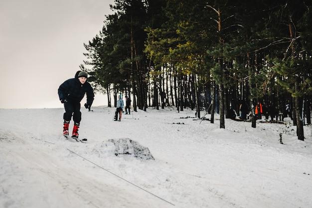 Mannen rijden op skisprongen vanaf een heuvel vanaf een springplank skischans op sneeuw in de karpaten. detailopname. winter natuur. de man rijdt op snelheid op sneeuw.