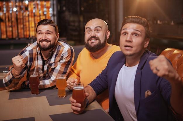Mannen schreeuwen tijdens het kijken naar voetbalwedstrijd in bier pub