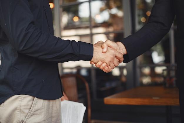 Mannen schudden elkaar de hand. bijlage van een zakelijke overeenkomst. begrip tussen zakenpartners.