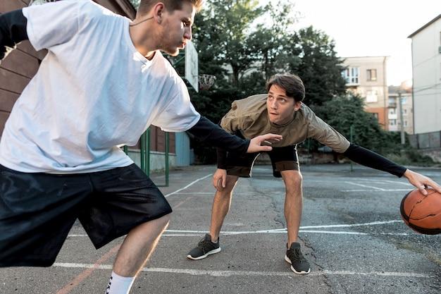 Mannen spelen basketbal op stedelijk hof