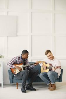 Mannen spelen gitaar. muziek schrijven. afrikaanse en blanke mannen.