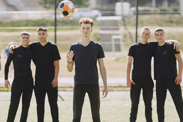 Mannen spelen voetballer in het park. toernooi op mini-footbal. kerel in zwarte sportpakken.