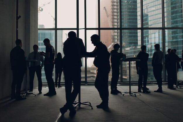 Mannen staan aan de tafels op de achtergrond van het raam