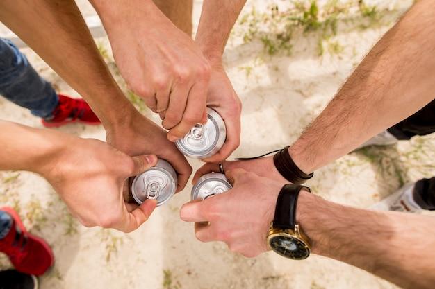 Mannen staan dicht bij elkaar en openen bier