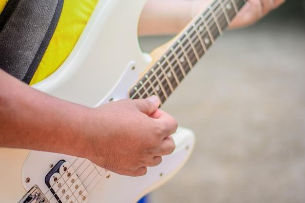 Mannen staan gitaar spelen overdag.