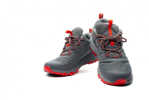 Mannen trekking schoenen geïsoleerd. grijs-rode wandelschoenen. veiligheidsschoenen voor klimmen. adventure uitrusting. lichtgewicht rubberen trekkingschoenen met veiligheid zool.