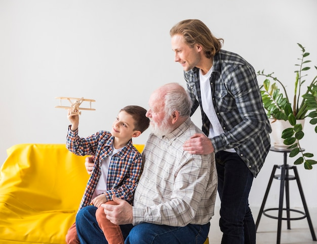 Mannen van verschillende generaties kijken naar speelgoed vliegtuig