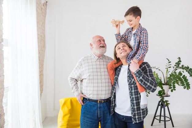 Mannen van verschillende generaties staan samen lachend tijdens het spelen