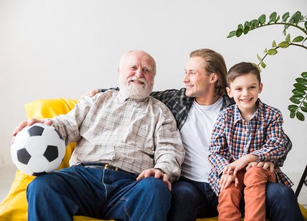 Mannen van verschillende generaties zitten op de bank