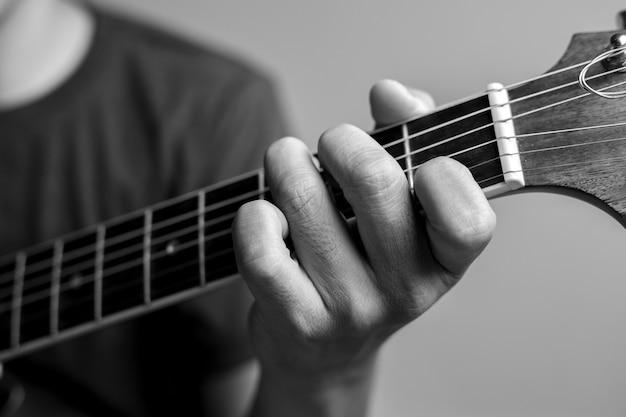 Mannen vangen akkoorden en leren gitaar spelen. close-up muzikanten vangen gitaarakkoorden. mannelijke muzikanten houden akkoorden vast en tokkelen gitaar.