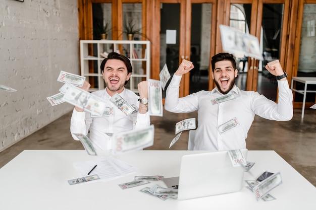 Mannen verdienen veel geld op kantoor, dollars vallen uit de lucht