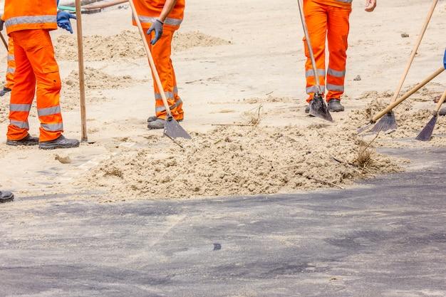 Mannen verwijderen zand van de promenade na de kater