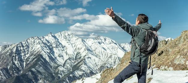 Mannen vieren succes door hun armen in besneeuwde bergen te verspreiden. realisatie van hun doelen