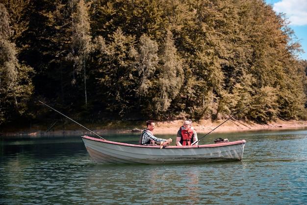 Mannen vissen in een rustig meer vanaf een boot