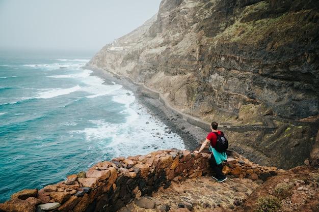 Mannen wandelaar met rugzak op de schilderachtige kustweg. de route voert langs enorme vulkanische rotswanden boven de brullende oceaan en komt samen met de steden cruzinha en ponta do sol. santo antao. kaapverdië.