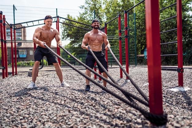 Mannen werken hard met touw op straat gym tuin. outdoor training. concept van fitness, sport, sporten, training en levensstijl.