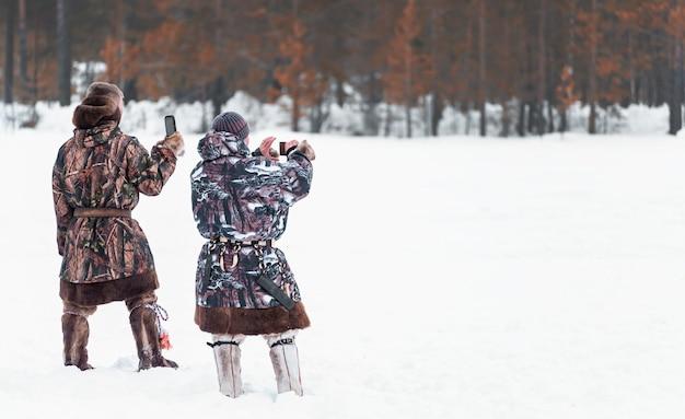 Mannen worden gefotografeerd op telefoons. feestdag van de dag van de rendieren noordelijke volkeren