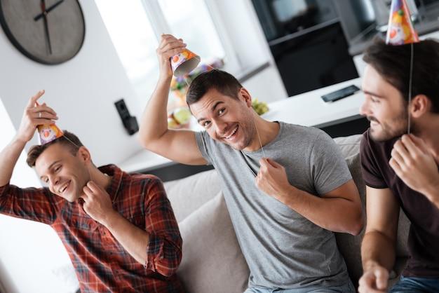 Mannen zetten verjaardagshoeden op. jongens bereiden feestje voor.