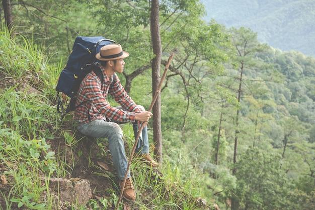 Mannen zitten en kijken naar bergen in tropische bossen met rugzakken in het bos. avontuur, reizen, klimmen.