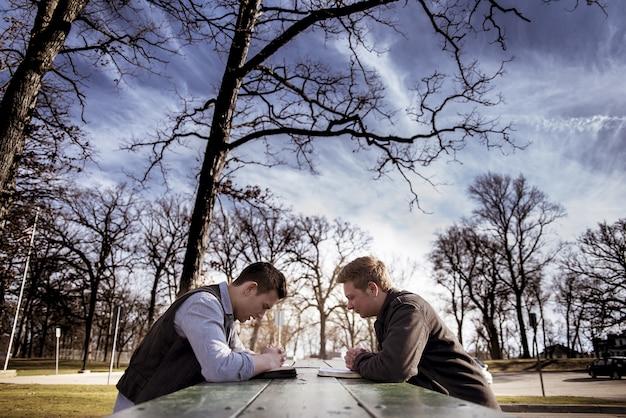 Mannen zitten op een bankje met bijbels en bidden in een tuin onder zonlicht met een onscherpe achtergrond