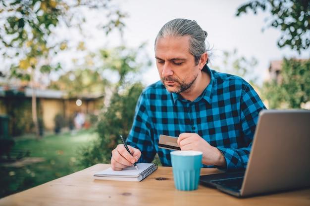 Mannen zitten op het terras in de achtertuin en notities op te schrijven