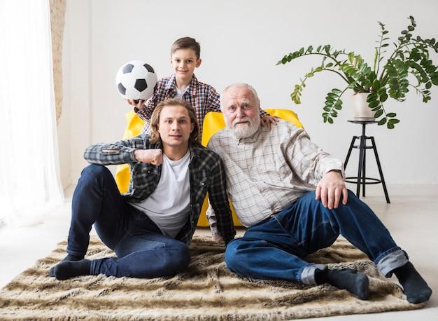 Mannen zitten op tapijt en kijken naar voetbal