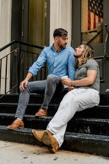 Mannen zitten op trappen en kletsen