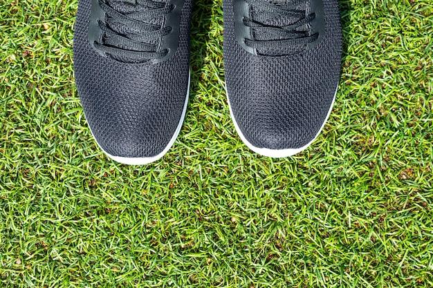Mannen zwarte sneakers met witte zolen close-up op kunstgras.