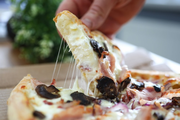 Mannenarmen nemen groot stuk knapperige verse pizza op werktafel close-up
