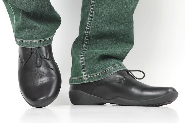 Mannenbenen in jeans en zwarte klassieke schoenen op witte achtergrond