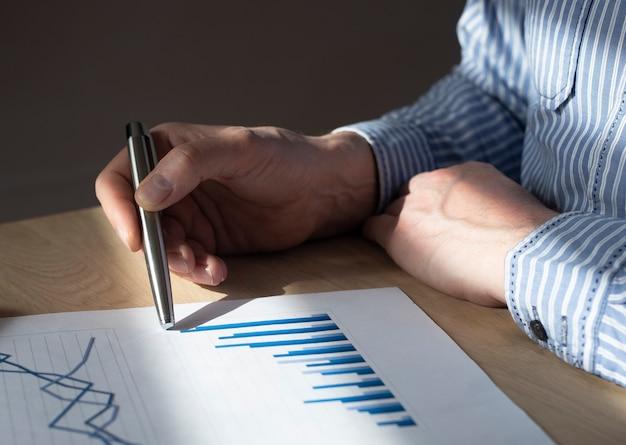 Mannenhand aan balie met financieel document met grafiek van groeiende trend. concept van economische groei, inkomensverhoging en zakelijk succes.