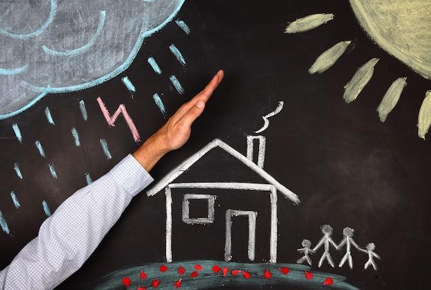 Mannenhand beschermt een huis en gezin