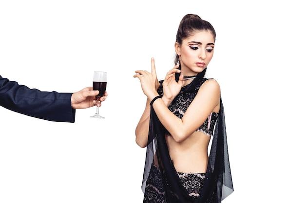 Mannenhand biedt een jong meisje een glas wijn aan. vrouw weigert alcohol te drinken. geïsoleerd op wit