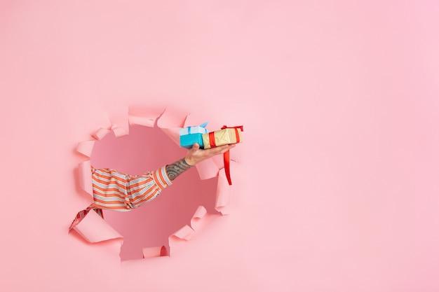Mannenhand cadeau geven in gescheurde koraal papier gat muur viering