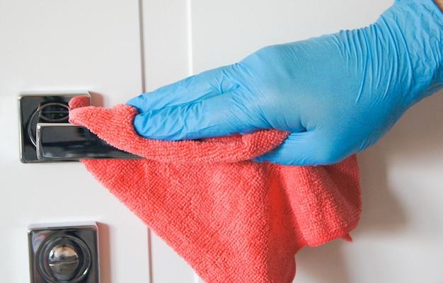 Mannenhand desinfecteren en wassen van deurklinken in blauwe handschoenen preventie van coronavirusinfectie tijdens de covid in blauw rubber