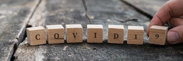 Mannenhand die een covid 19-teken maakt dat op houten blokken wordt gespeld.