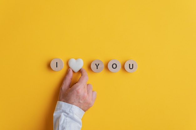 Mannenhand die een i love you-bord maakt, gespeld op houten uitgesneden cirkels met een marmeren hartvorm in het midden.