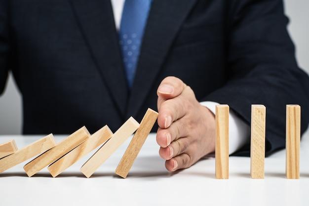 Mannenhand die het domino-effect stoppen. risicobeheersing concept.