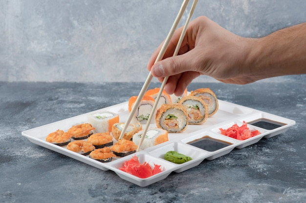 Mannenhand die sushibroodje met eetstokjes van de witte plaat neemt