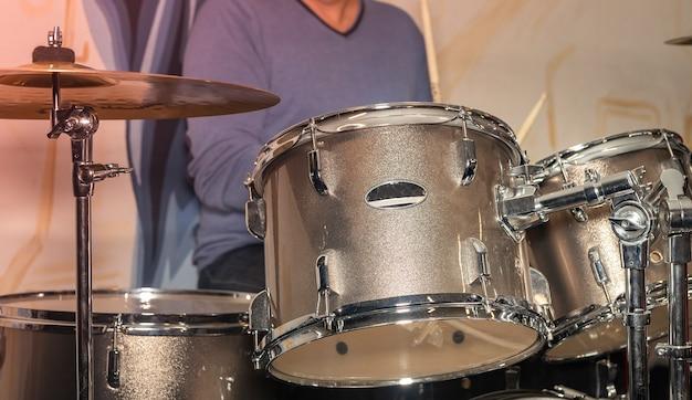 Mannenhand en drums met metalen platen.
