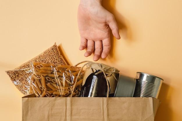 Mannenhand en papieren zak met voedselvoorziening crisis voor quarantaine