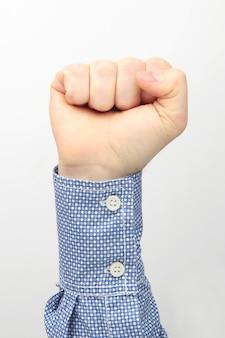 Mannenhand gebalde in een vuist op een wit oppervlak