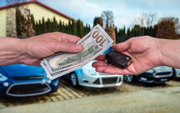 Mannenhand geeft geld en neemt autosleutels, nieuwe auto als achtergrond. financiën
