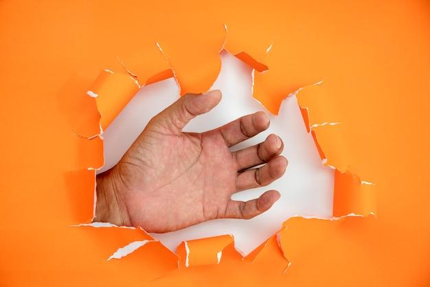 Mannenhand gescheurd oranje papier
