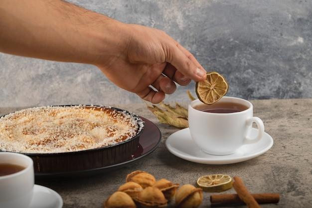 Mannenhand gesneden citroen bovenop thee op stenen tafel.