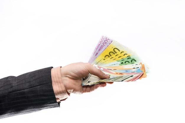 Mannenhand geven eurobankbiljetten geïsoleerd op een witte muur