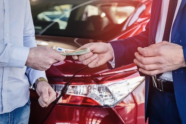 Mannenhand geven eurobankbiljetten voor dealer close-up