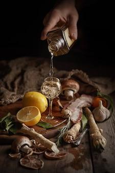 Mannenhand giet alcohol in een glas ... samenstelling van verschillende levensmiddelen op een houten tafel. bovenaanzicht
