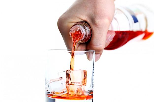 Mannenhand giet drankje voor een cocktail