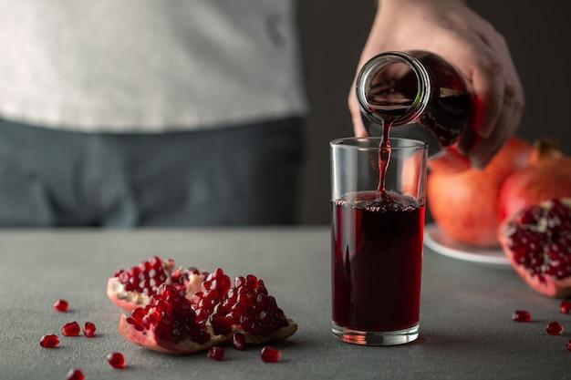 Mannenhand granaatappelsap uit een fles gieten in een glas